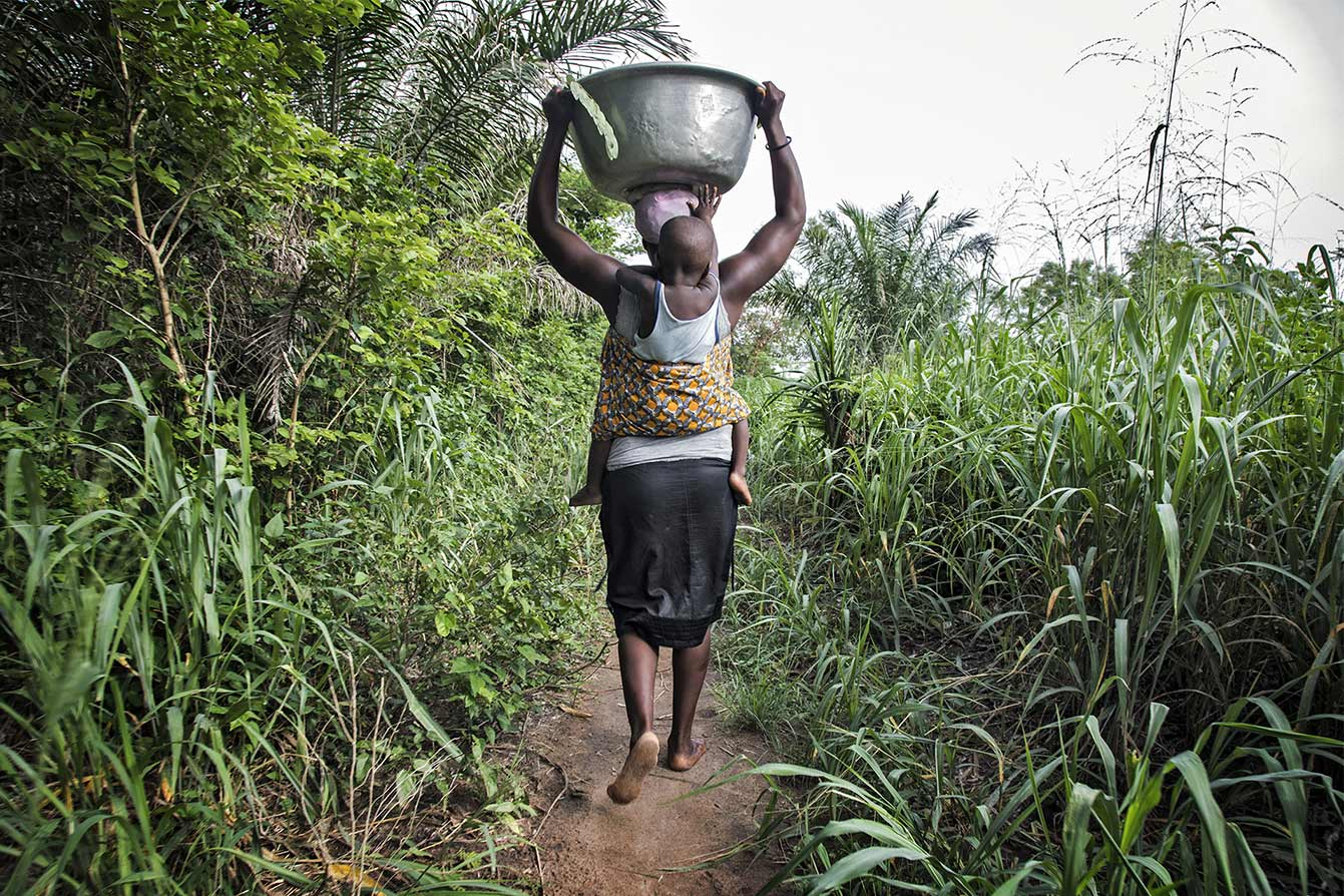Donna porta una bacinella d'acqua sulla testa. Reportage fotografico sull'energia in Africa.